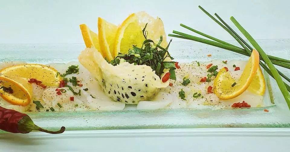 Carpaccio von der Jakobsmuschel, Orangen-Oliven-Emulsion, Löwenzahnsalat im Parmesankörbchen