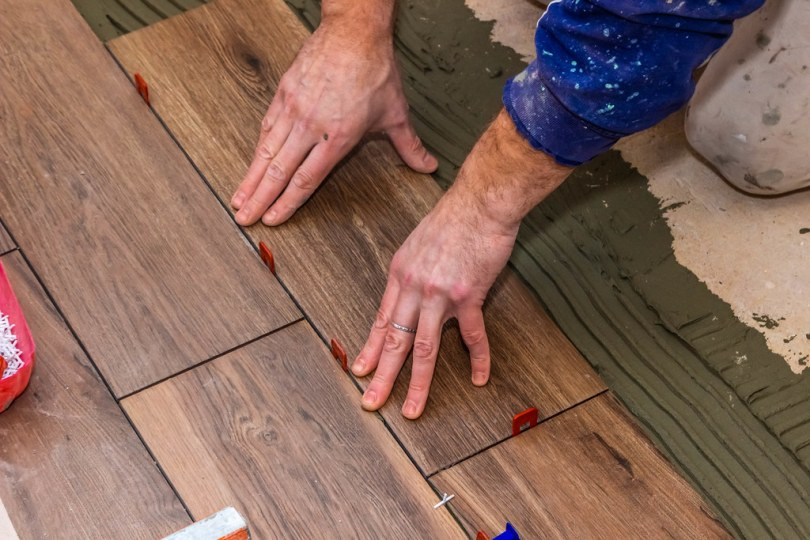 Tiler placing tiles with a tile leveling system