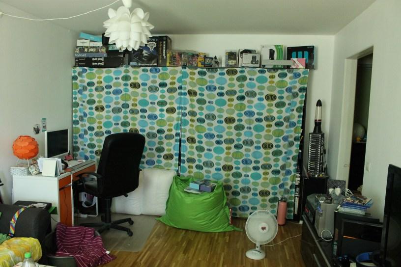Vardagsrummet före. Mitt skrivbord och hyllor efter hela väggen.