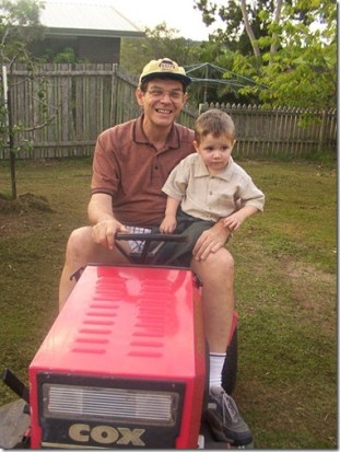 Zeke with Papa Gear on the lawnmower - 2