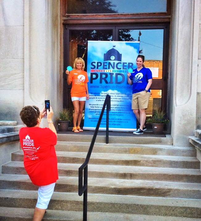 Here, Judi Epp takes a photo of Kim Fidler & Katie Zuber outside the courthouse before the 2015 Spencer Pride Festival.