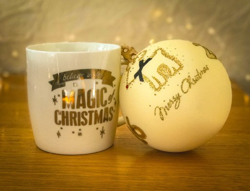 Christmas Mug saying Magic of christmas. sitting next to a bauble with a glittery reindeer. Wording on the bauble says merry christmas.