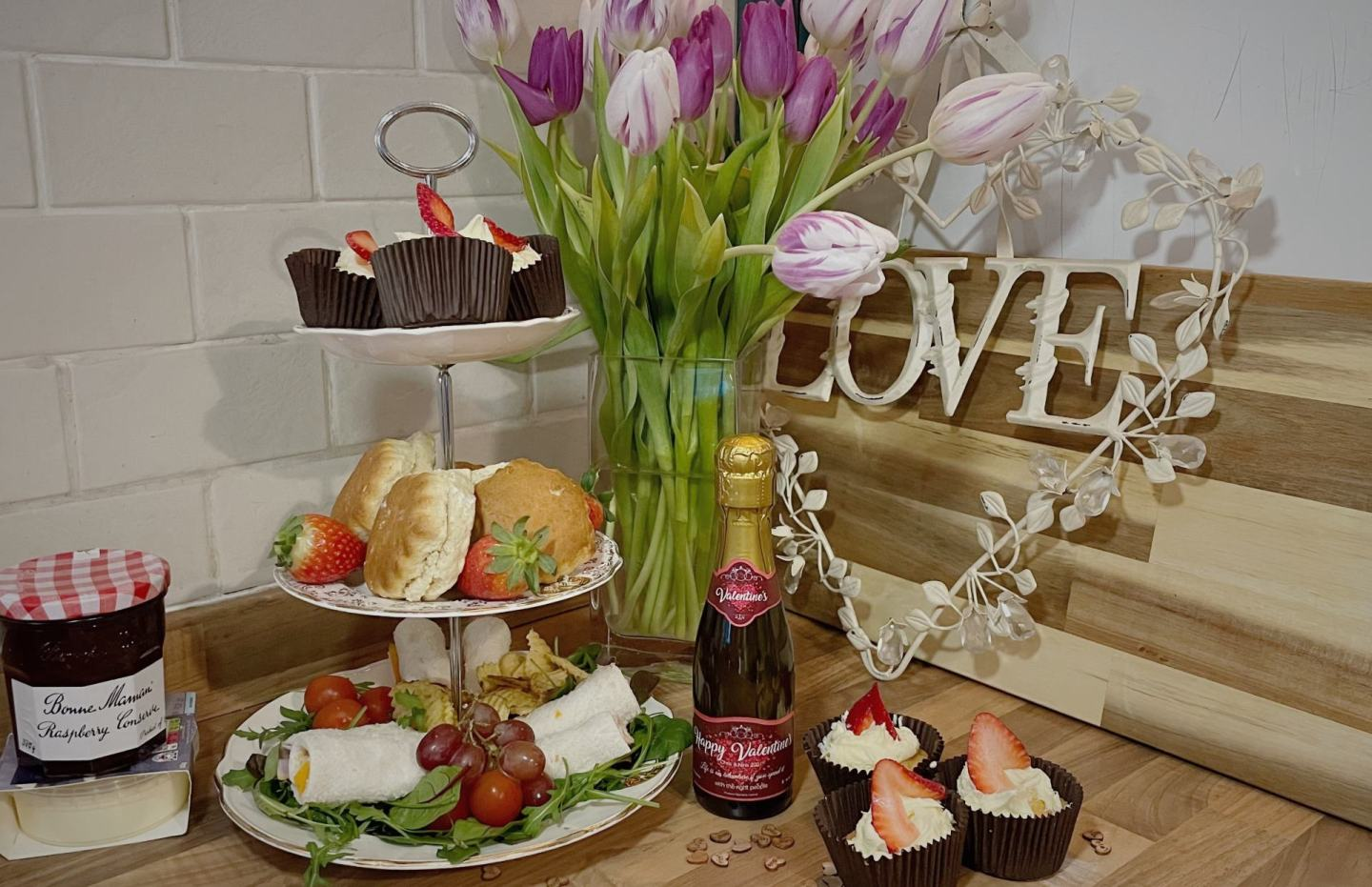 afternoon tea spread with scones, cupcakes and sandwich rolls on a three tier cake stand with a metal love sign behind. bottle of personalised prosecco in the middle of picture.