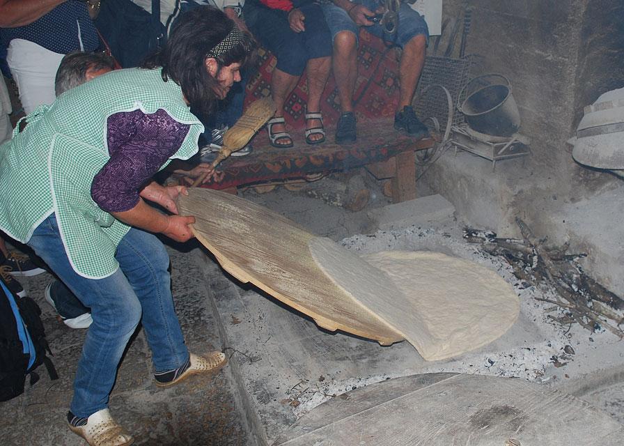 Soparniken läggs sedan på en häll där det tidigare eldats. När soparniken är på plats sopas aska och glöd över bakverket. Gräddas i ca 15 minuter och sopas sedan ren. Penslas med olivolja och beströs med finhackad vitlök.