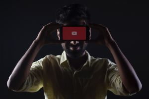 Man covering face with phone with youtube logo in red with black background