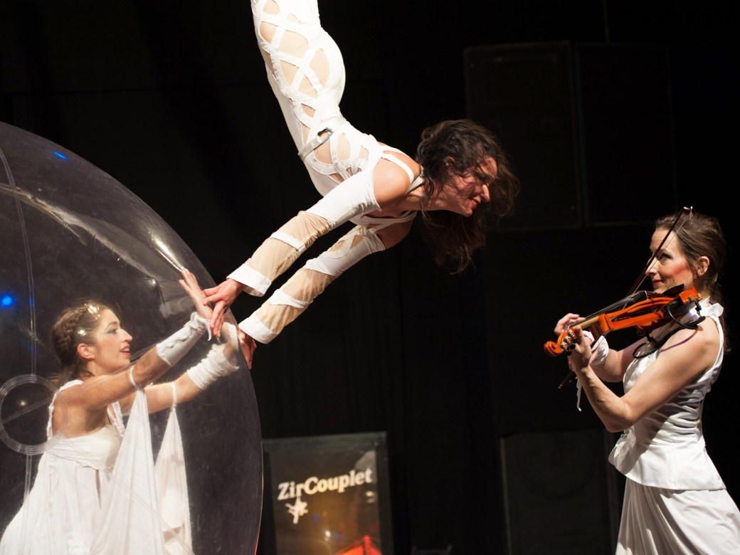 a dancer in a plastic ball playing, dancing with a trapezes acrobat and a violinist.