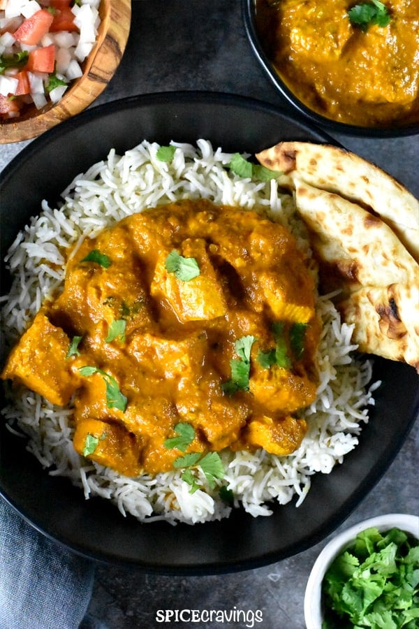 A bowl with chicken tikka masala served ver rice, along with garlic naan