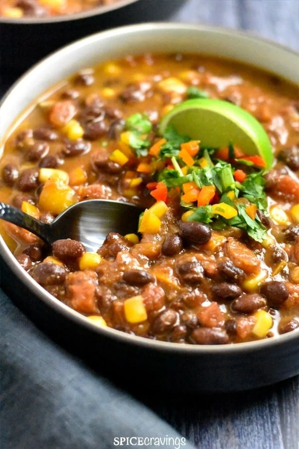 Dipping a spoon in a bowl of black bean chili made in Instant Pot