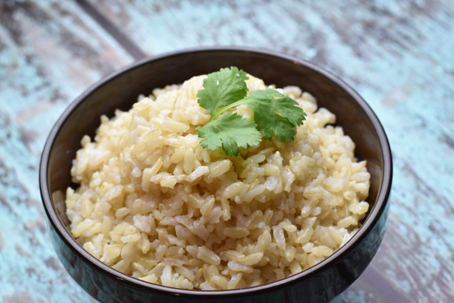 Brown rice cooked in Instant pot, served in brown stone bowl, garnished with cilantro leaves