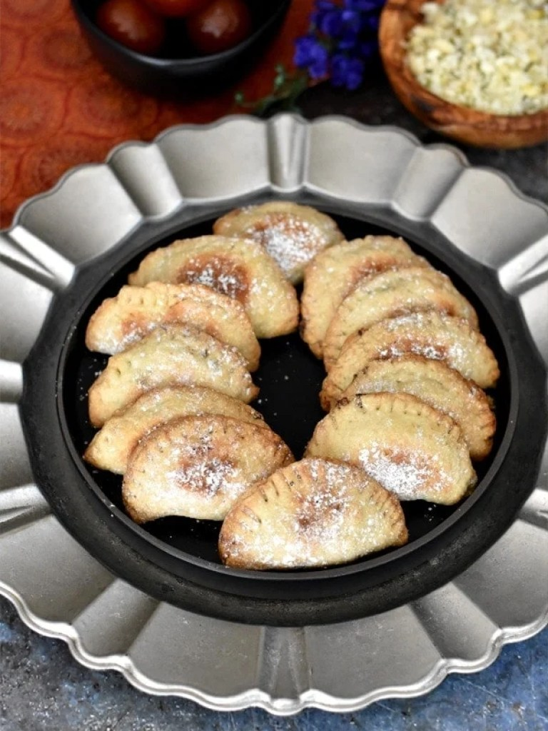 Baked Gujiya by Spice Cravings. Gujiya, or Milk Fudge Turnovers, are a popular dessert made in the northern part of India around the festivals of Holi and Diwali. This recipe is an oven baked version of the traditional deep fried gujiya, which is a sweet dumpling that is made by stuffing pastry dough with sweetened milk fudge (khoya), chopped nuts and coconut flakes and is glazed with a thick sugar syrup. #cooking #food #recipe #recipes #foodphotography #foodblogger #yummy #delicious #foodie