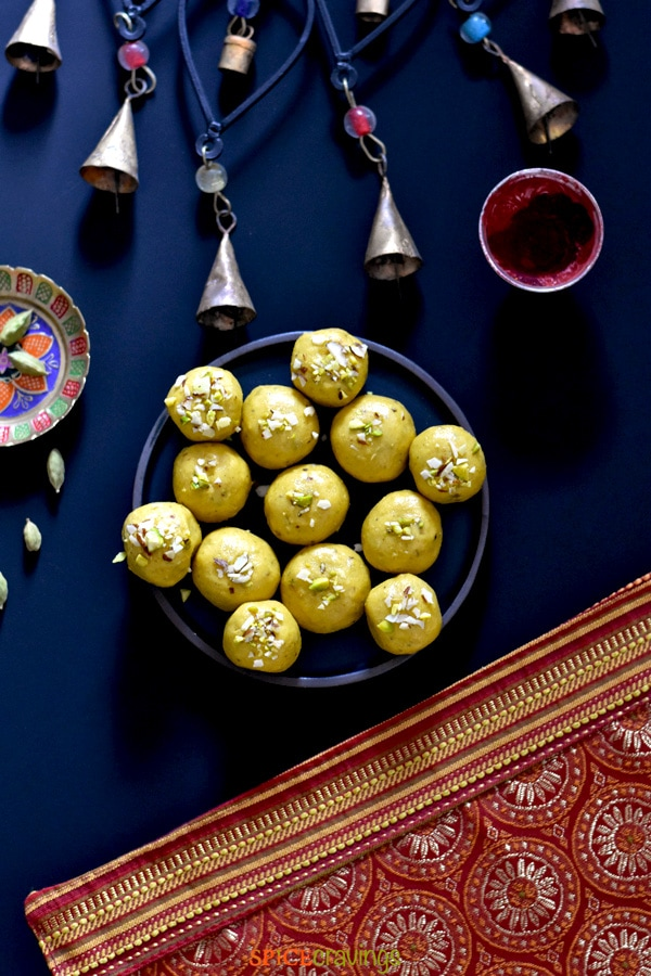 A plate of besan ladoo, chickpea flour fudge, placed next to bells on a decorative placemat
