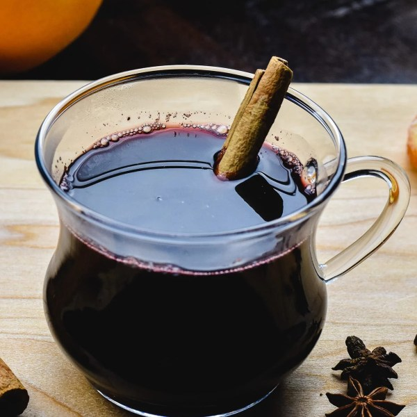 A cup of gluhwein, mulled wine on a board with spices