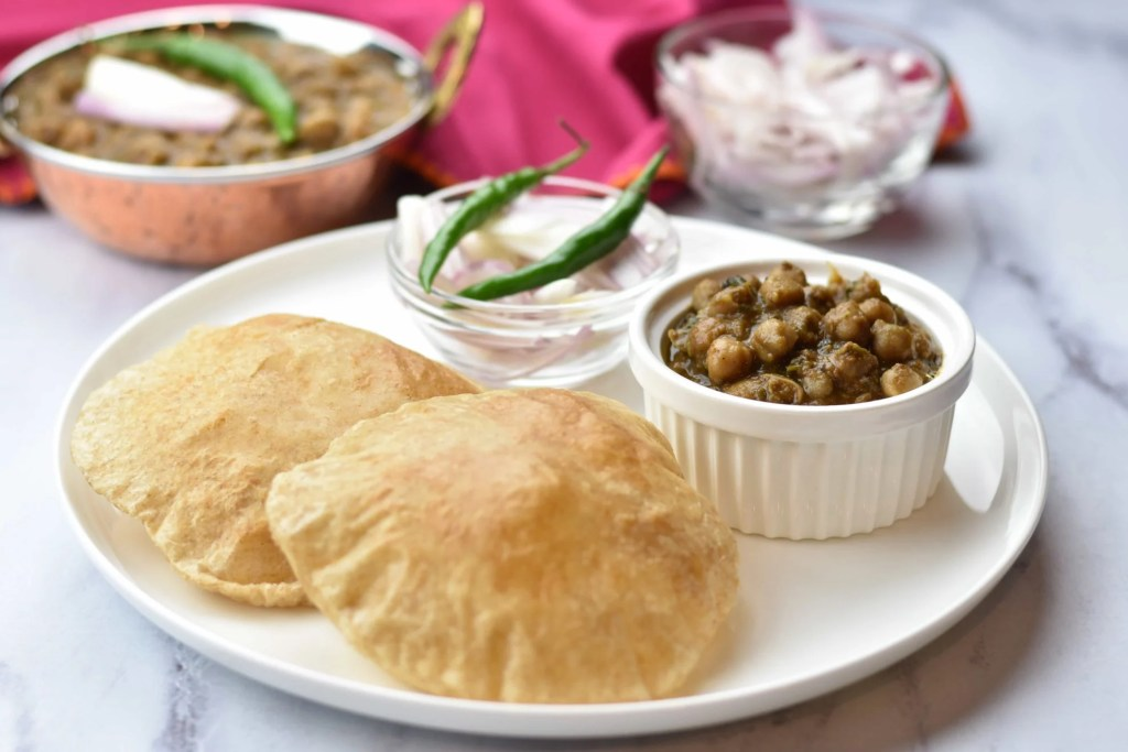 Chole Bhature, by Spice Cravings. Chole Bhature is a popular dish from the Punjabi cuisine in Northern India, where a Chickpeas curry, called Chole (Cho-lay), is served with a puffed, deep-fried bread, called Bhatura (Buh-too-ray). #cooking #food #recipe #recipes #foodphotography #foodblogger #yummy #delicious #foodie