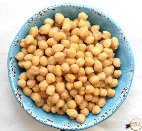 Cooked Chickpeas in a blue bowl and white background