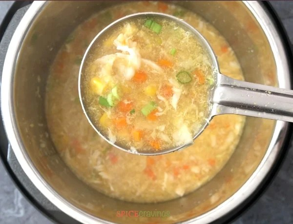 A ladle of chicken sweet corn soup in the Instant Pot pressure cooker