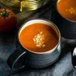 A cup of Roasted Red Pepper Tomato Soup garnished with parmesan cheese