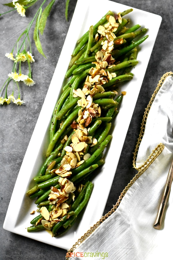 String beans steamed and sautéed with almonds and served on a gray backdrop