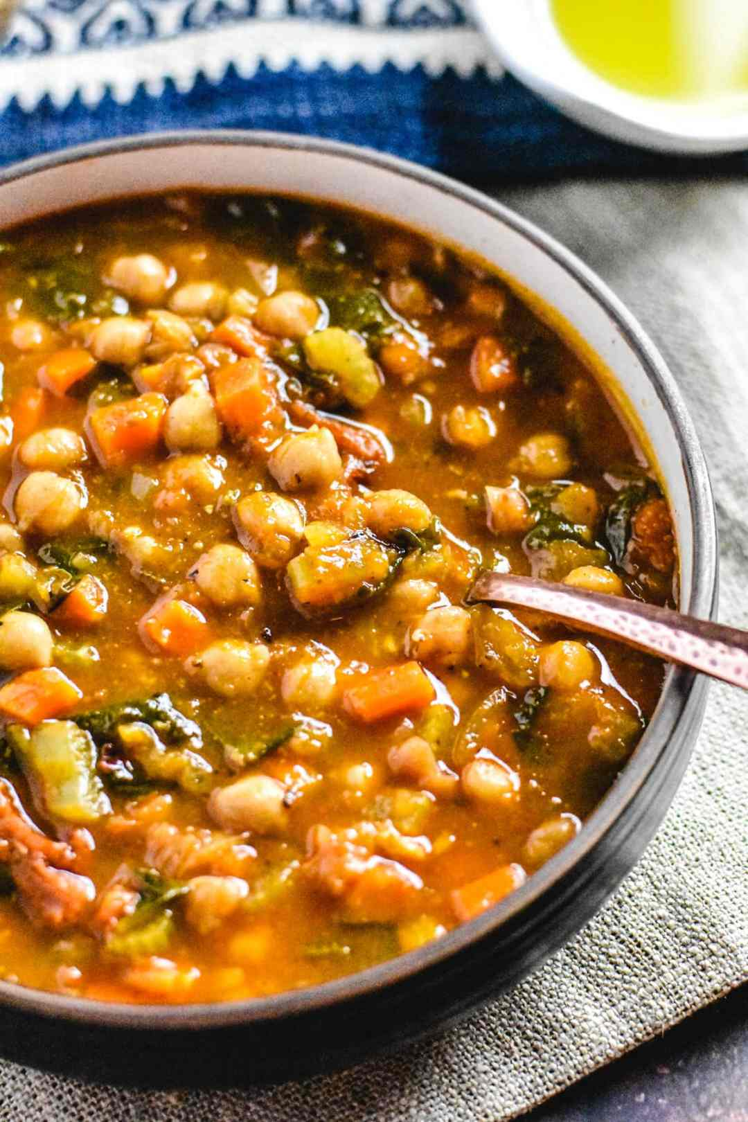 A slice of toasted baguette soaking in Moroccan Chickpea Soup bowl