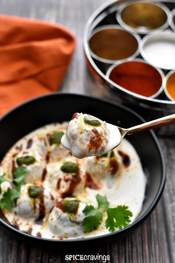 A spoonful of dahi bhalle with cilantro chutney and tamarind chutney