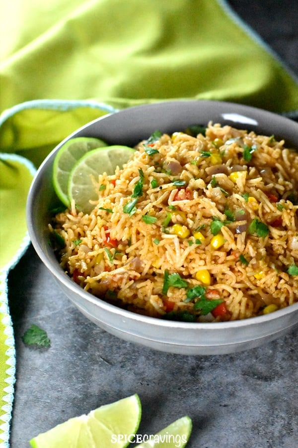 Mexican rice with corn and peppers, garnished with cilantro and lime