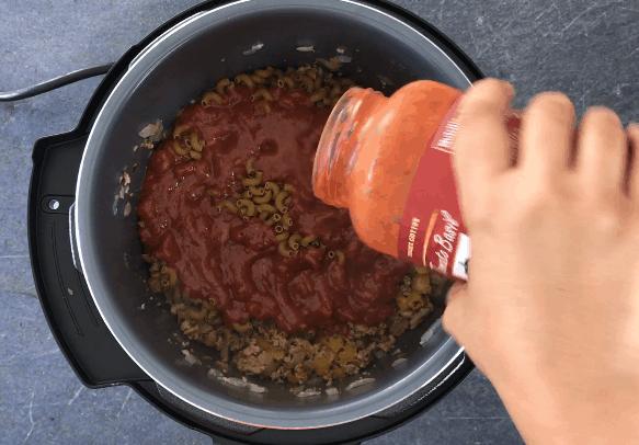 Adding marinara sauce to the pot to make Goulash