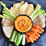 Red pepper hummus served with chips and veggies