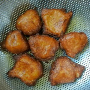 apple churro fritters draining in metal colander