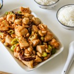 A plate of Kung Pao Chicken with tea and steamed rice