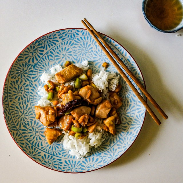 Kung Pao chicken over steamed rice with tea and chopsticks
