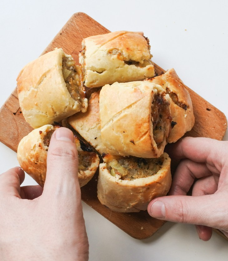 hands grabbing sausage rolls off a cutting board
