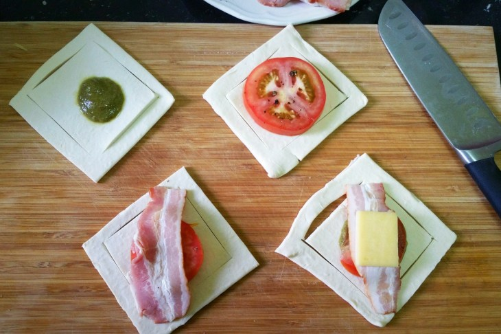 cut puff pastry squares with pesto, tomato slice, bacon and cheese on them