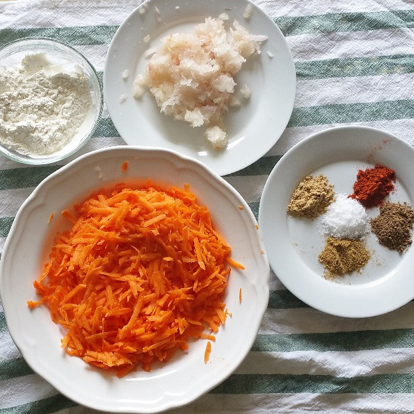 Combine grated carrots and onion in a mixing bowl and combine. Sprinkle with spices and sea salt and toss together. Add cornstarch and flour and combine to make a dough. Using your hands or a tablespoon, form dough into balls around 1in/2cm in diameter.