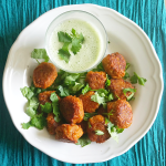 Carrot bhaji with yogurt dipping sauce garnished with fresh cilantro