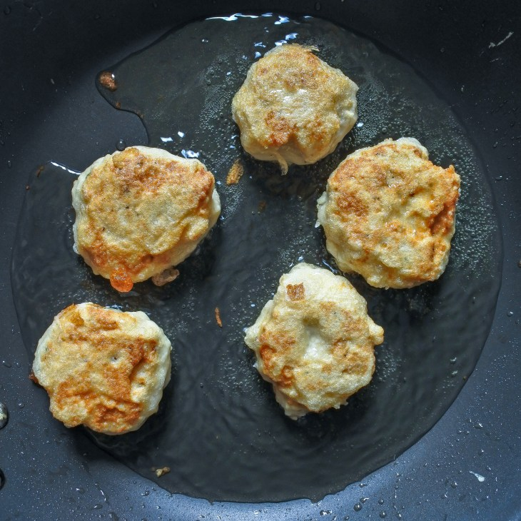 chicken nuggets lightly frying in pan with oil