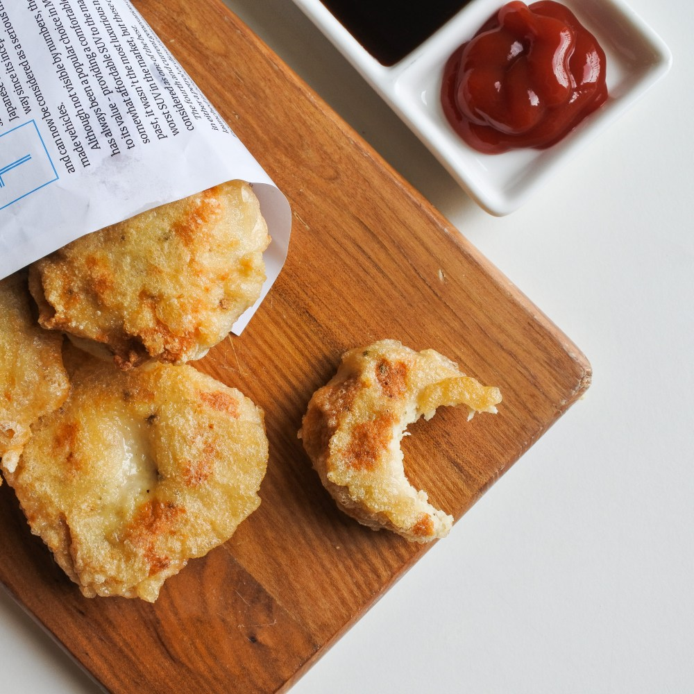 chicken nuggets on board with dipping sauce