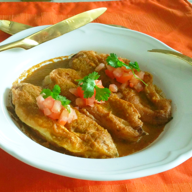 Chiles Rellenos in a bowl with sauce and garnished with chopped tomatoes and cilantro
