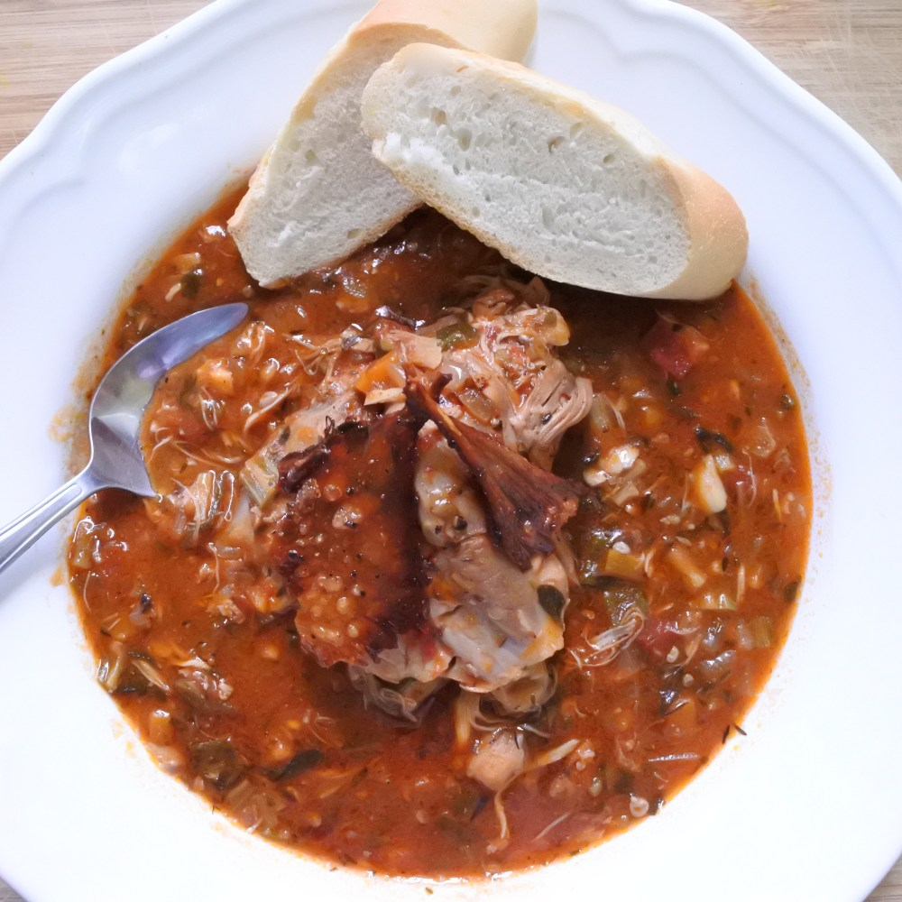 Chicken thigh atop Cajun stew with crispy skin garnish and bread