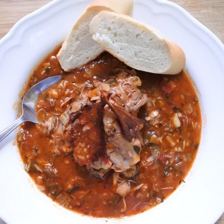 Chicken thigh atop Cajun stew with crispy skin garnish and bread