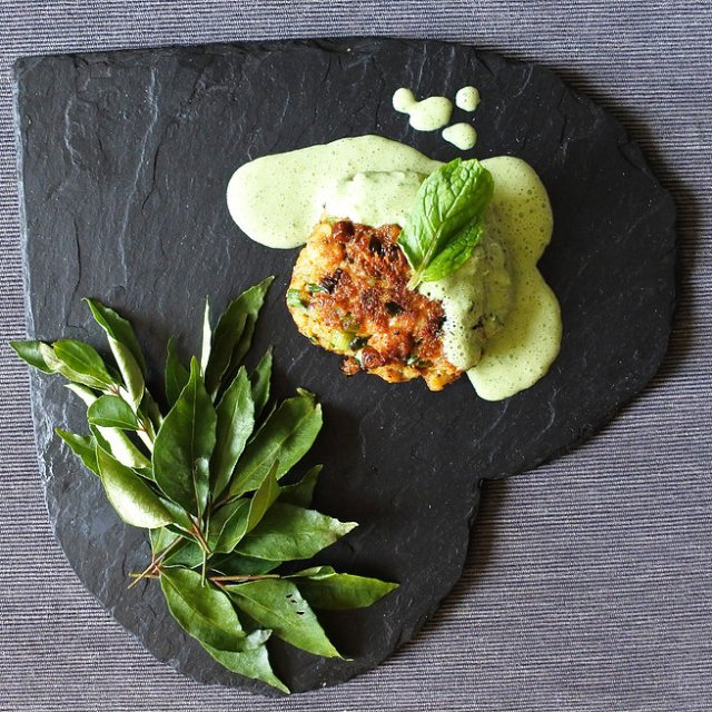 fish cake drizzled with a mint yogurt sauce next to curry leaves on heart shaped slate