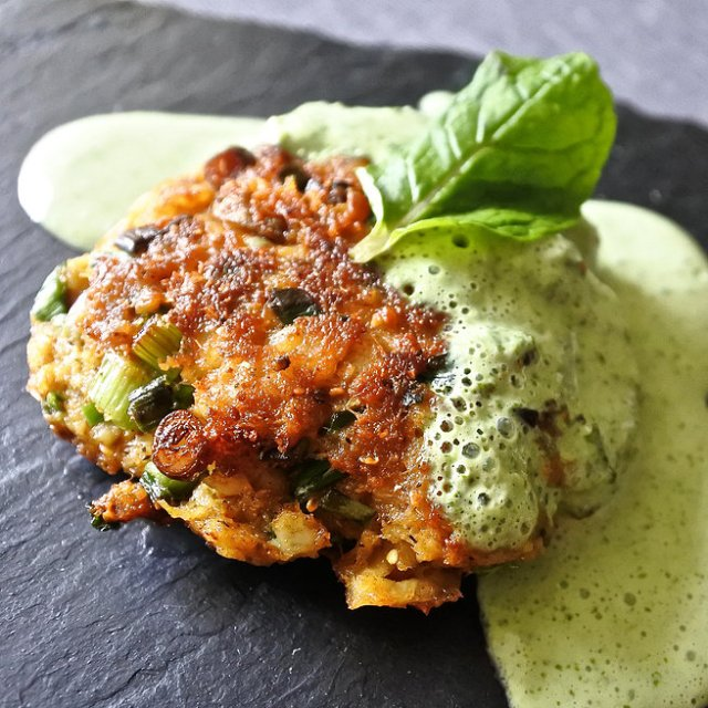 fish cake drizzled with a mint yogurt sauce next to curry leaves