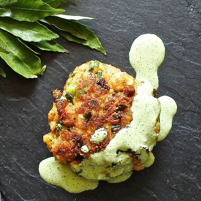 Indian spiced fish cake drizzled with a mint yogurt sauce next to curry leaves