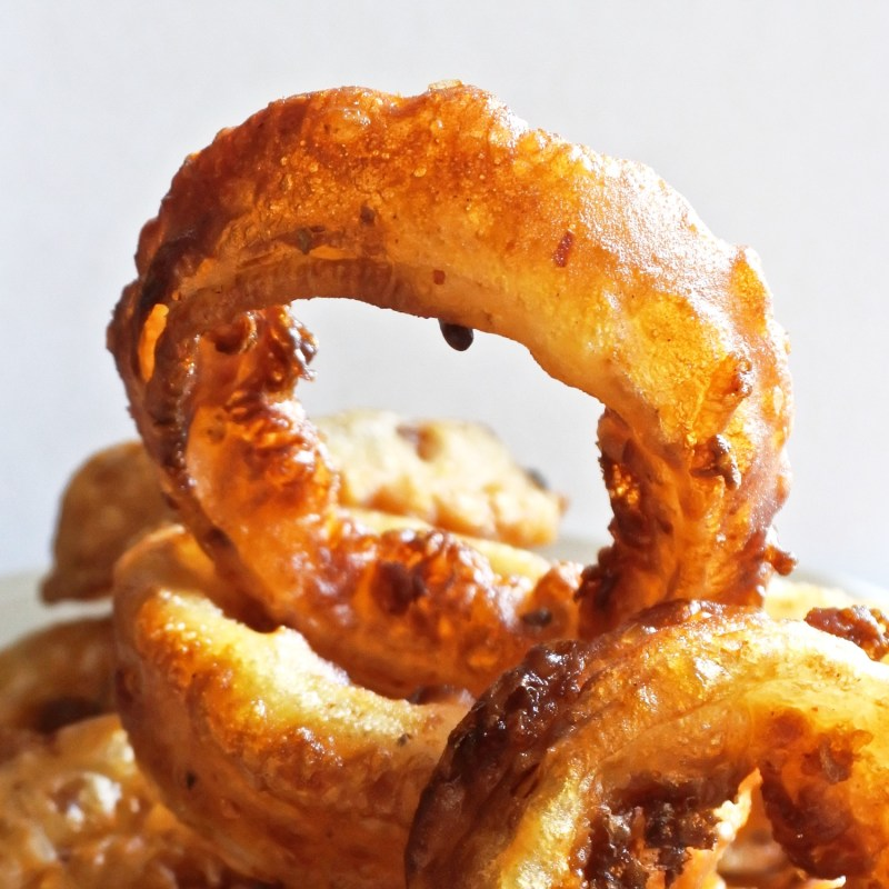 fried onion ring atop of a mound of onions rings