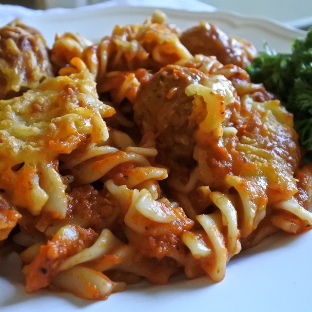 corkscrew pasta baked in sauce with meatballs and melted cheese topping