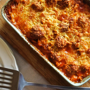 A casserole dish of pasta and meatballs covered in melted cheese with plate and spatula