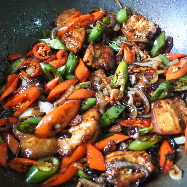 twice fried pork belly, onions and chilis frying in Chinese black bean sauce