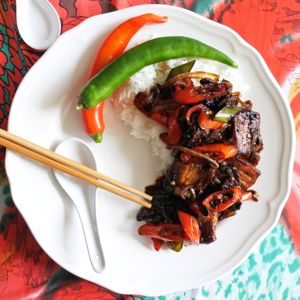 Fried pork belly in Chinese black bean sauce with peppers and onions over rice