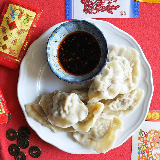 Pork Dumplings on plate with dipping sauce, red envelopes and old Chinese coins
