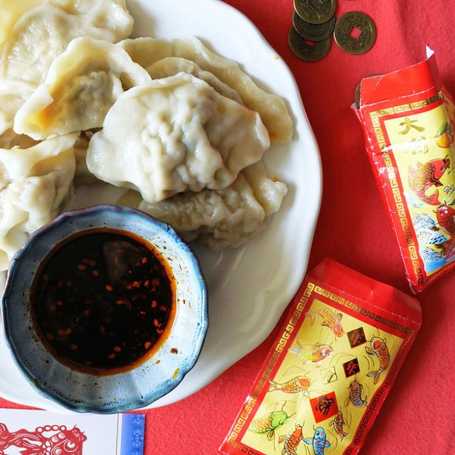 pork dumplings on plate with Chinese chile oil, red envelopes and old Chinese coins