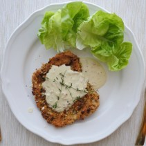 Pistachio encrusted pork loin cutlet with cream sauce and lettuce