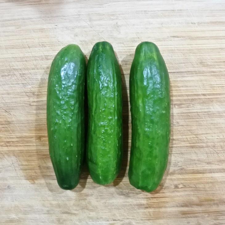 three cucumbers on a cutting board